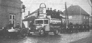Quickborn - Kieler Straße, 1937 (Foto: Pinneberger Tageblatt 06.01.1937); Transparentaufschrift: 'Wer gibt nichts in die Spendenbüchse? Der Spießer und der Meckerfritze'