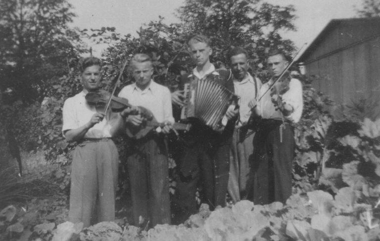 Aufnahme von ca. 1943 vor der Baracke in der Uetersener Straße in Tornesch. Fünf Personen sind abgebildet, zwei davon mit Geigen, ein Akkordeon und ein Mandolinenspieler. Von links: zwei Ukrainer Leotz und Joseph, dann der Pole Henryk Bejerski, dann die beiden Ukrainer Dimit Noworad und Kasimirsch. Sie machten privat sonntags Musik. Foto von Hans-Joachim Wohlenberg.